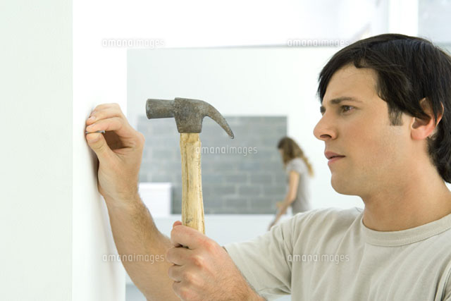 Man hammering nail into wall, woman