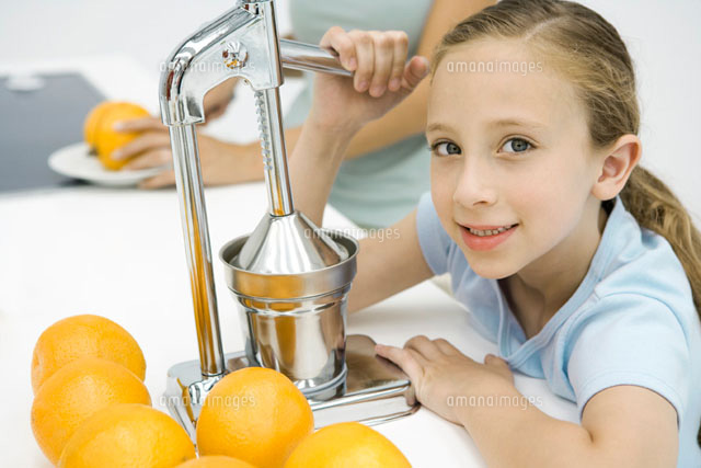 Little girl making fresh orange juice with citrus press
