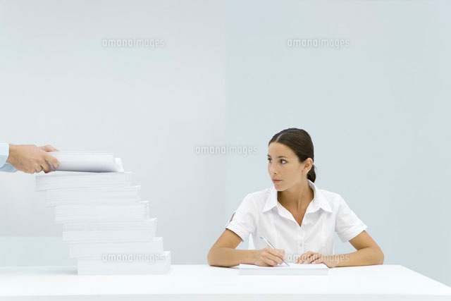 Woman sitting at table, looking at staggered stack of paper