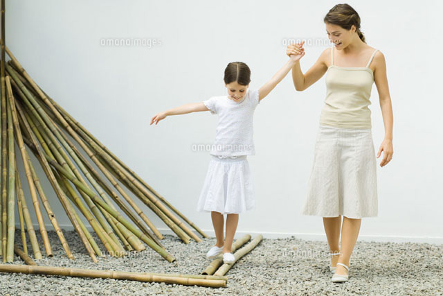 Girl balancing on bamboo, mother helping her