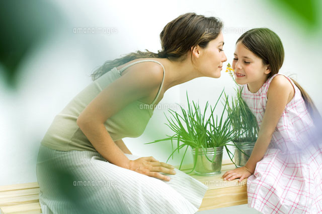 Woman and daughter smelling flower sprig together