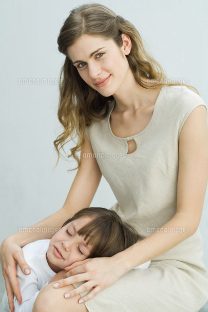 Little boy resting head on mother's lap