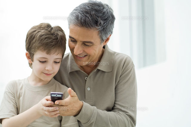 Mature man and young son looking at cell phone together