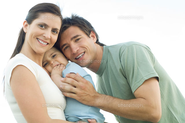 Family smiling at camera, mother holding baby daughter