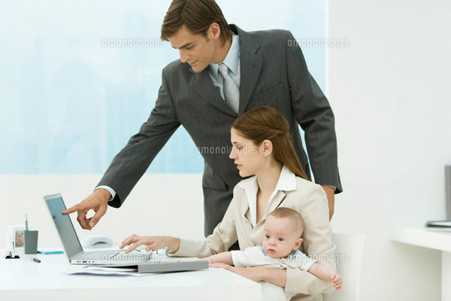 Professional woman in office, holding baby on lap
