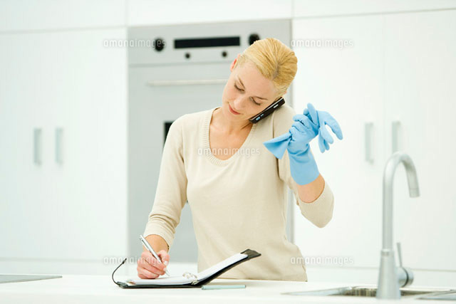 Woman standing at kitchen sink, wearing rubber gloves