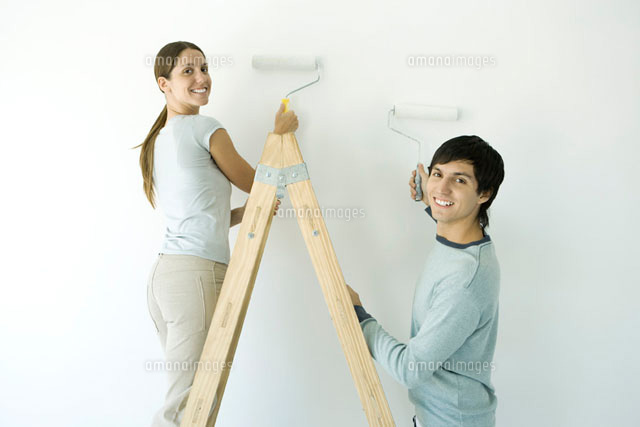 Couple painting wall with rollers over their shoulder