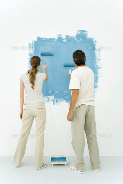 Couple painting wall blue using rollers, rear view