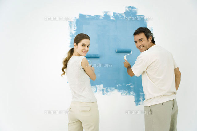 Couple painting wall blue using rollers