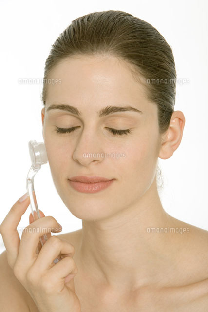Woman using exfoliator brush on face