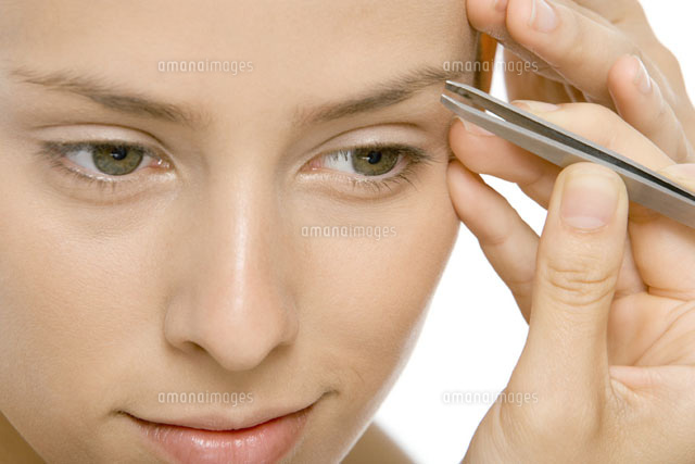 Woman using tweezers to pluck eyebrows,close-up