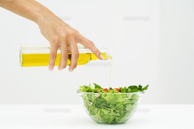 Woman pouring olive oil on salad,cropped view of hand
