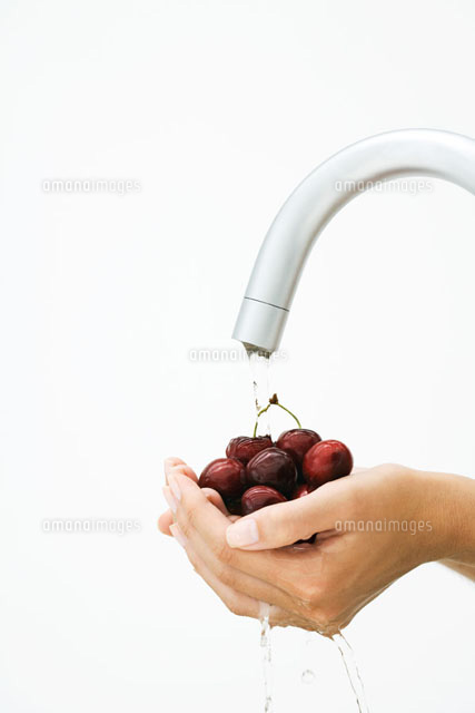 Woman rinsing handful of cherries under faucet