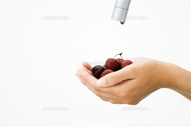 Woman holding handful of cherries under faucet