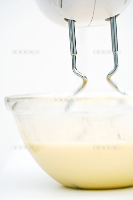 Electric mixer and bowl of batter,close-up