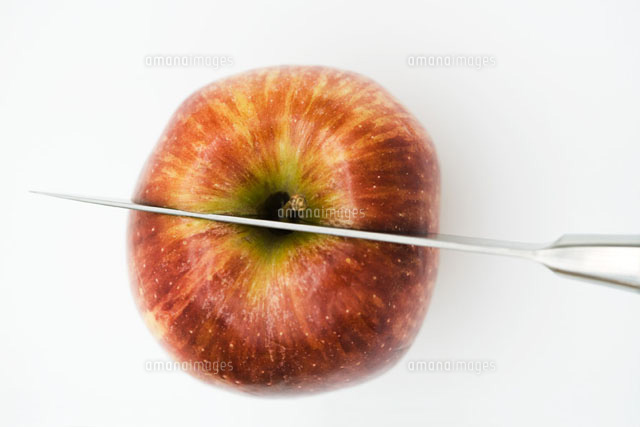 Knife cutting apple in half,high angle view,close-up