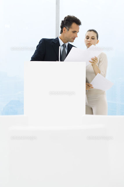 Businessman standing,female assistant holding up documents