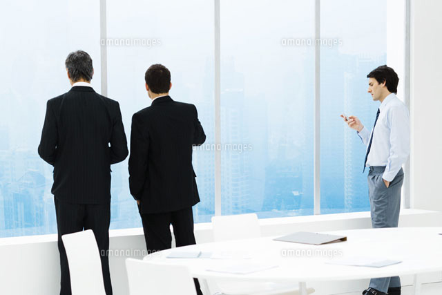 Businessmen standing by window in conference room
