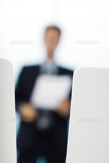 Blurred silhouette of businessman holding document