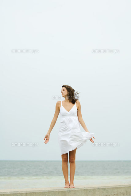 Girl in sundress standing at the beach,tousled by wind