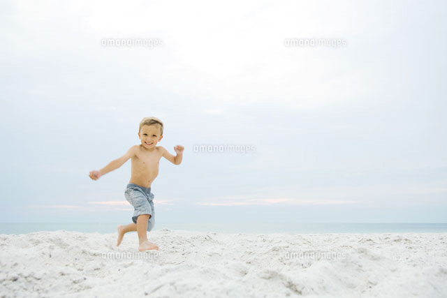 Little boy running at the beach,smiling at camera