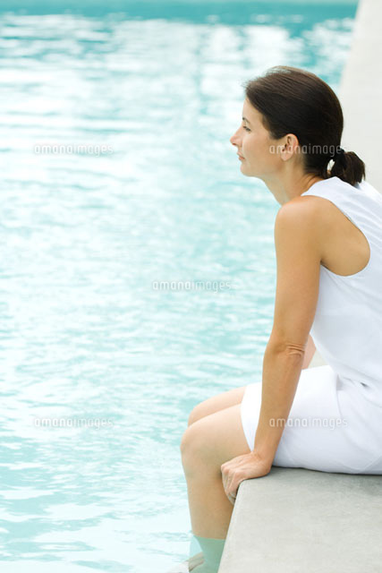 Woman sitting on edge of swimming pool