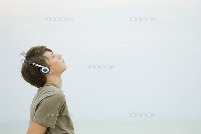 Teenage boy listening to headphones,looking up,side view