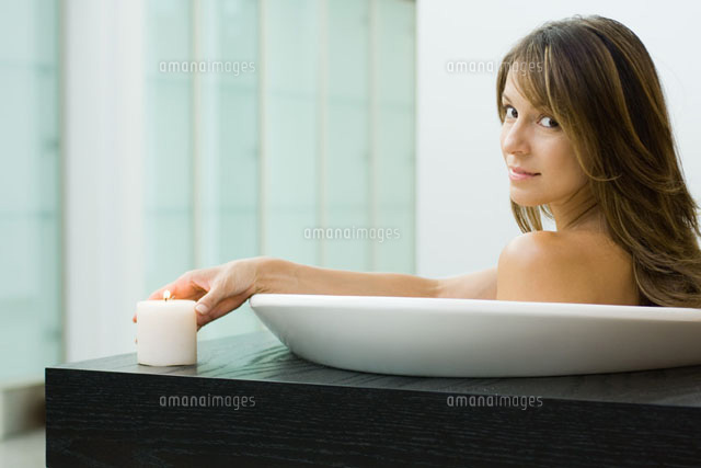 Woman sitting in bathtub,holding lit candle