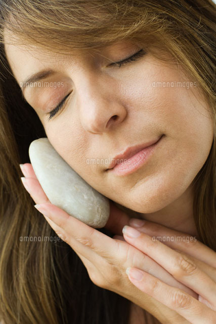 Woman holding smooth stone against cheek