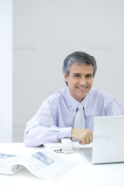 Businessman sitting at desk,smiling at camera