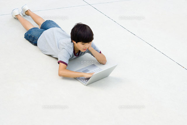 Boy lying on stomach on the ground,using laptop computer