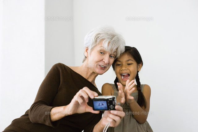 Woman photographing self and granddaughter with camera