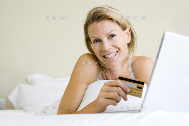Woman lying in bed with laptop,holding credit card