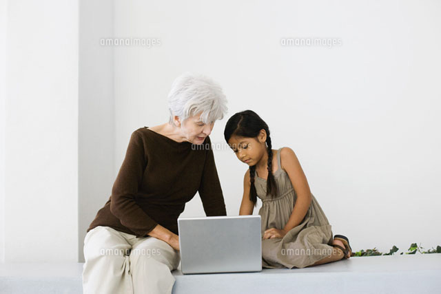 Senior woman and granddaughter using laptop together