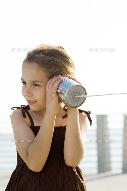 Little girl listening to tin can phone
