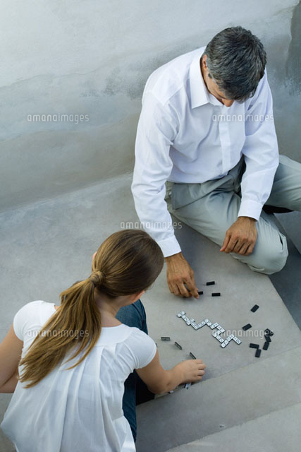 Father and daughter playing dominoes