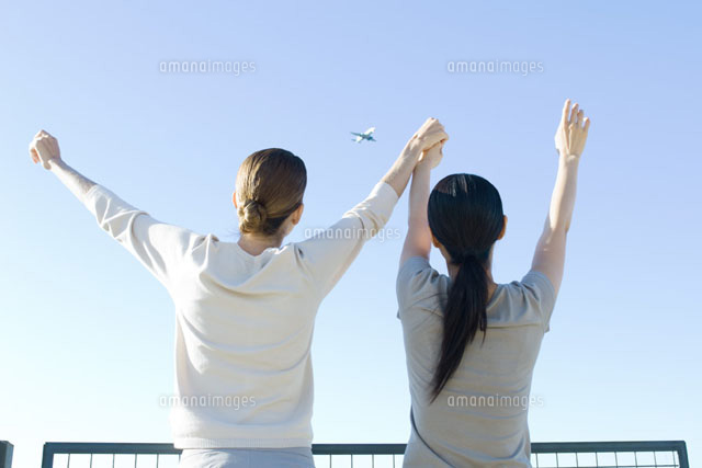 Women looking at airplane in sky,holding hands