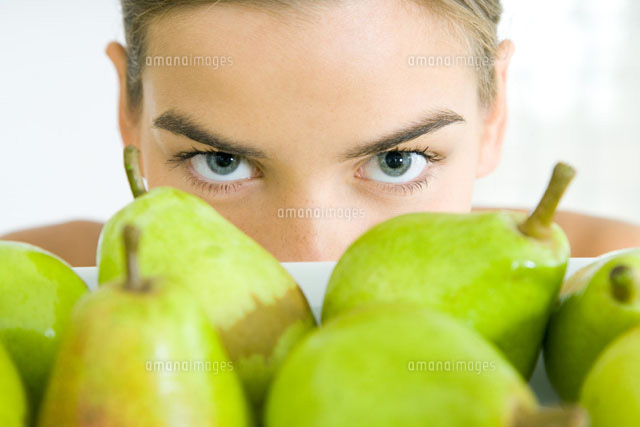 Young woman looking over tray of pears