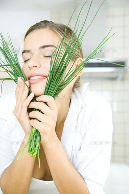 Young woman holding chives up to face,eyes closed