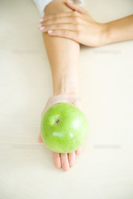 Apple resting in a woman's palm,high angle view
