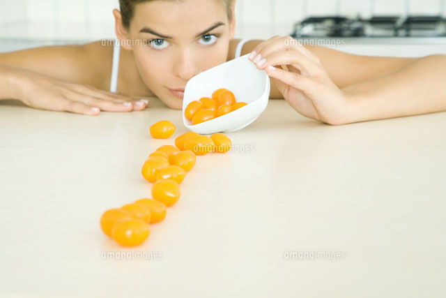 Woman spilling yellow cherry tomatoes out of a small dish