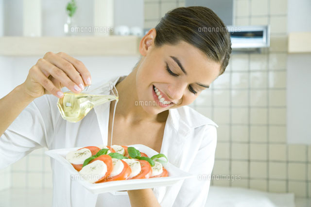 Young woman pouring olive oil over tomato mozzarella salad