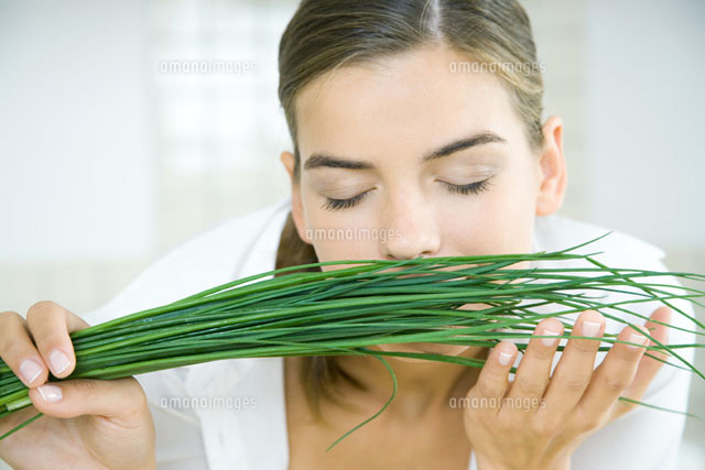 Young woman smelling a bunch of chives,eyes closed