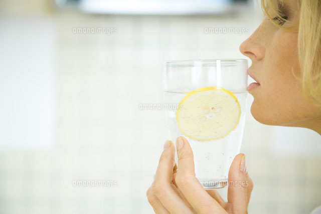 Woman holding a glass of water with a slice of lemon
