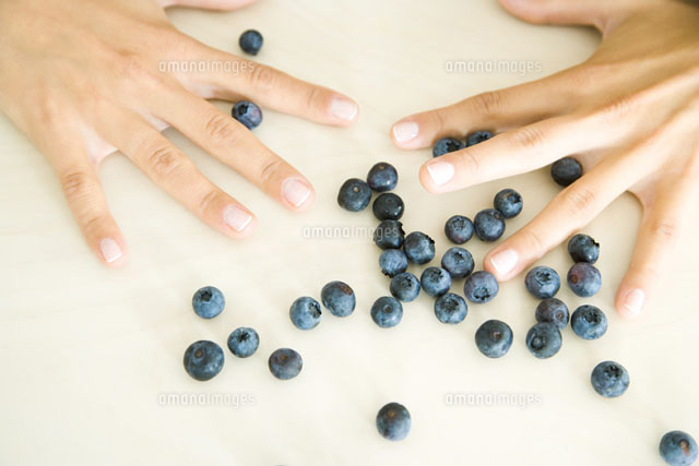 Hands with fingers spread above scattered blue berries