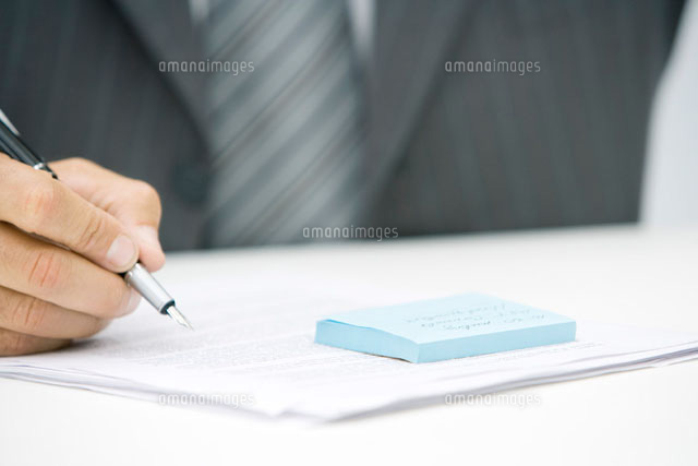 Man with adhesive note and document,holding pen
