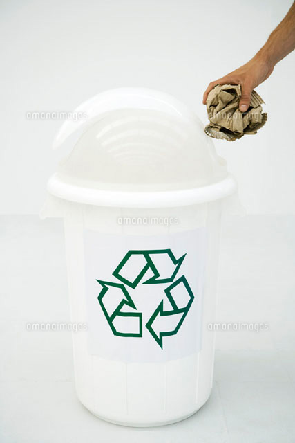 Man's hand placing cardboard in recycling bin,cropped