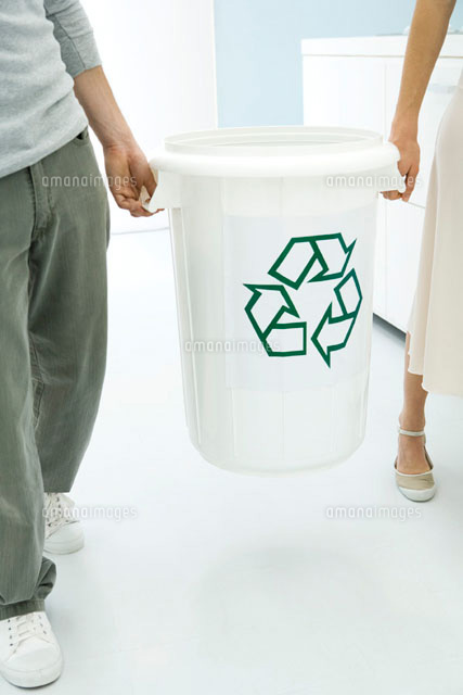 Two people carrying recycling bin together,cropped view