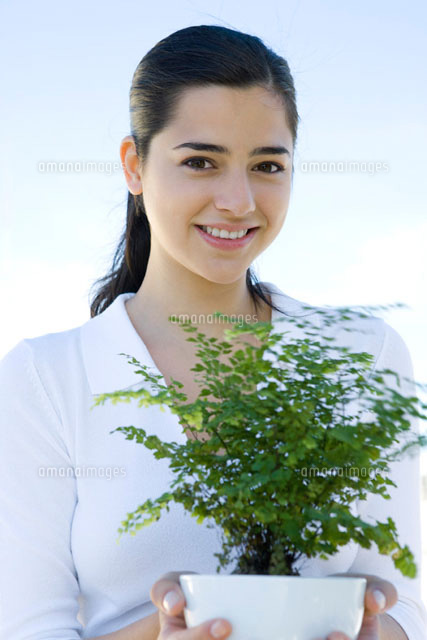 Young woman holding potted plant,smiling at camera