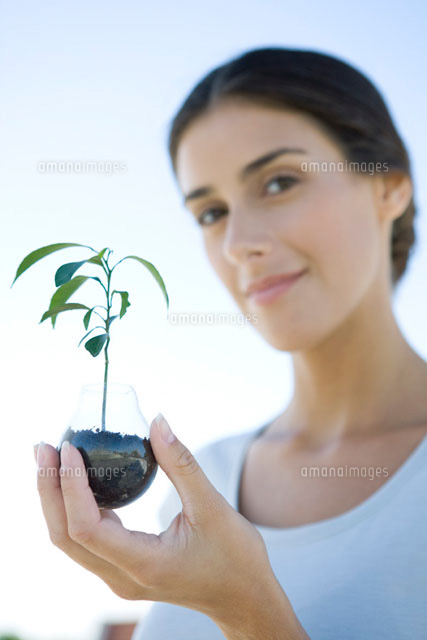 Woman holding potted seedling,smiling at camera